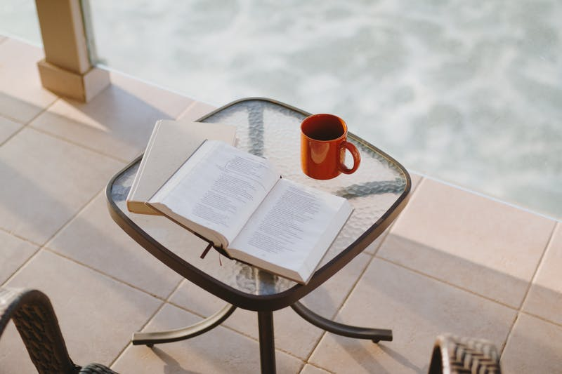 A book and coffee on a coffee table.