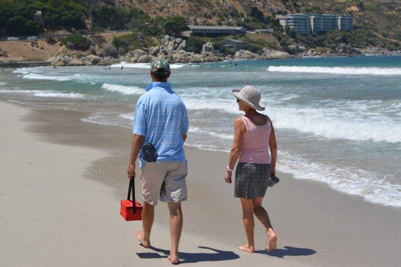 A couple walking on a beach in Hout Bay.