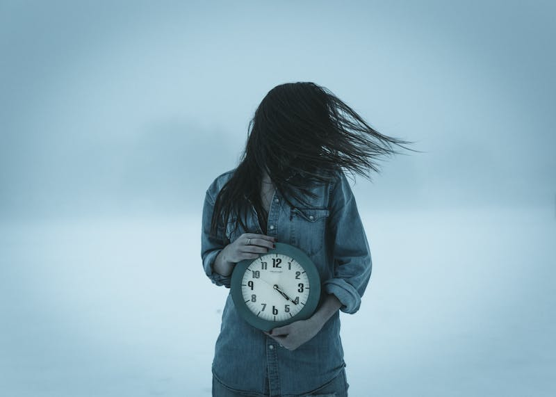 A girl holding a clock.
