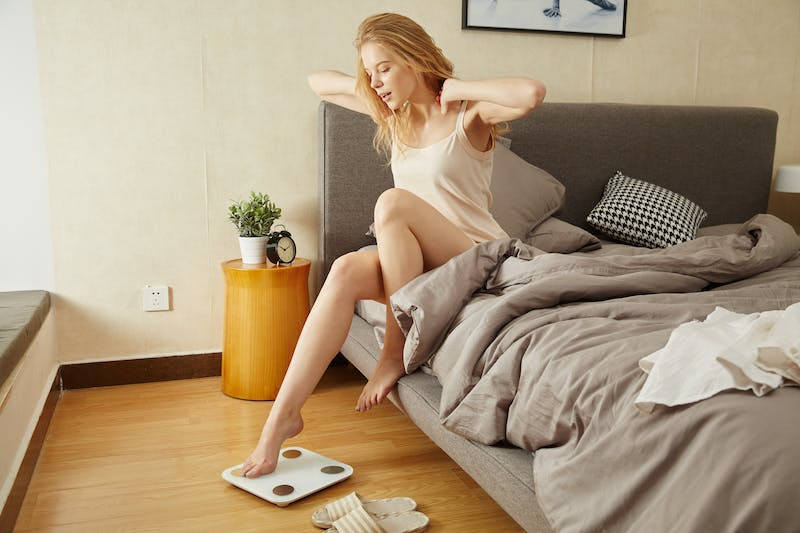 a blond woman getting out of bed and stretching