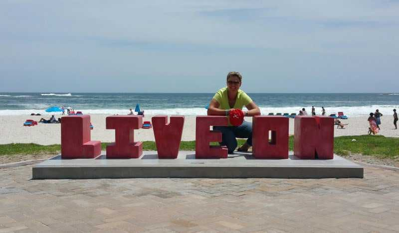 "Anita on camps bay beach crouching behind big letters: ""LIVE ON""."
