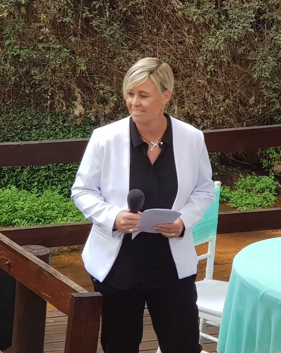 Anita speaking at wedding with microphone in hand.