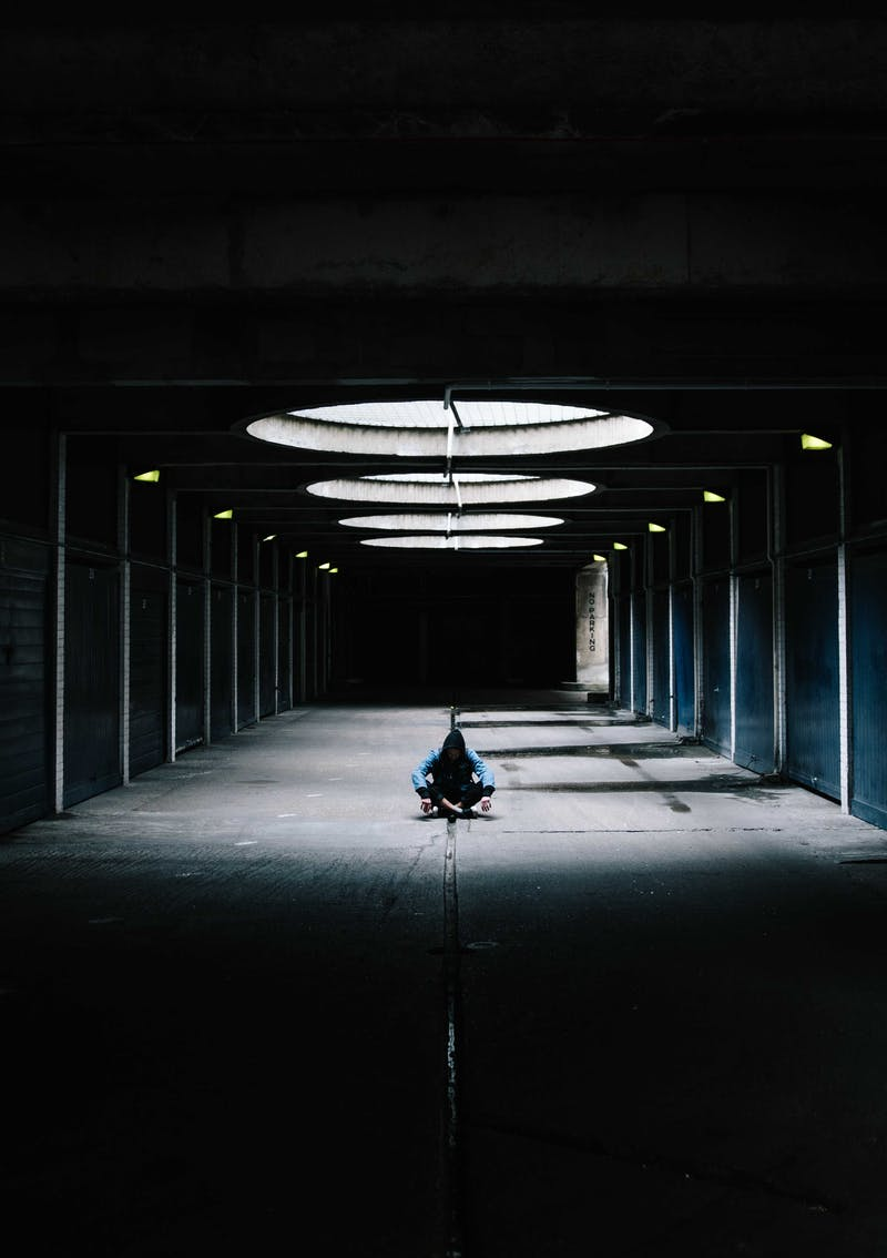 A picture of a boy/man sitting alone in a warehouse
