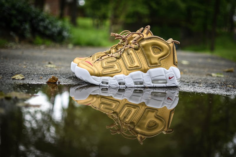 a single yellow takkie next to a puddle of water with SUP written on it