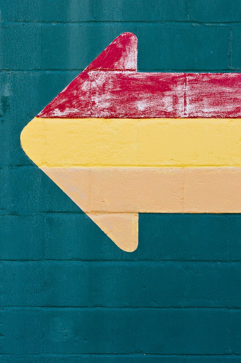 A colourful arrow on a green-painted wall. The arrow is a mixture of red, green and a kind of orange-white.