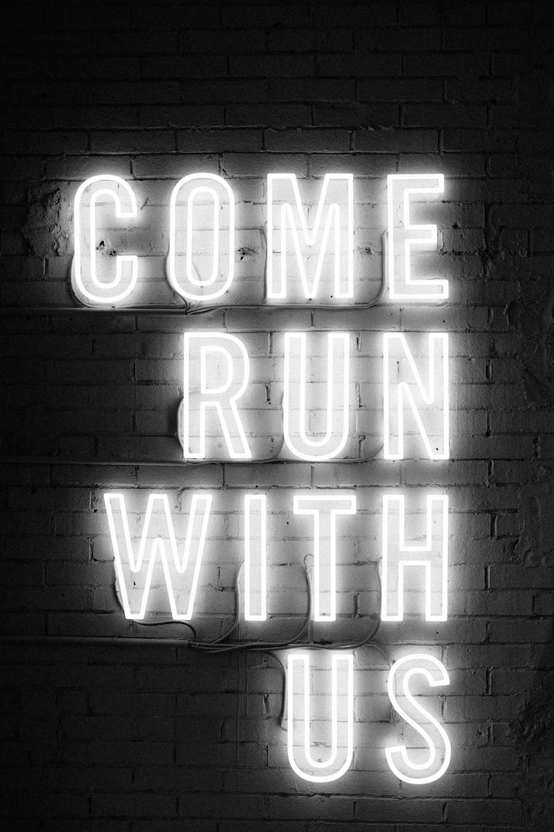 "A neon sign that says ""come run with us""."