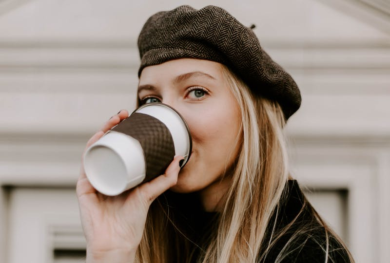 A blond woman with a black woolen beanie on drinking coffee out of a take away cup