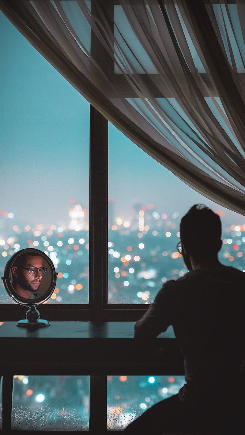 A man with a beard with his back to us looking into a mirror while looking at a view from an apartment  overlooking the city