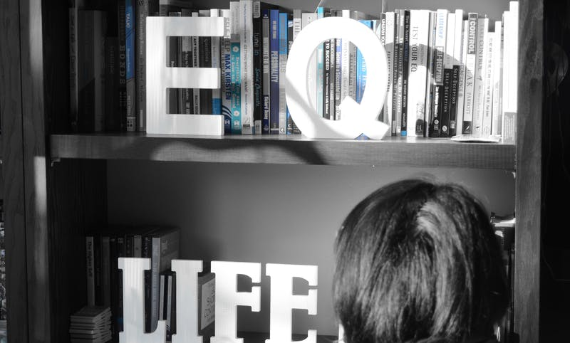 "Anita's life coaching room. Picture is in black and white with the letters ""EQ"" and ""LIFE"" on shelf."