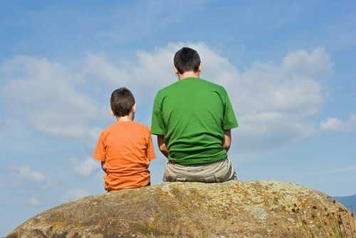 Father sitting next to his son on a rock.