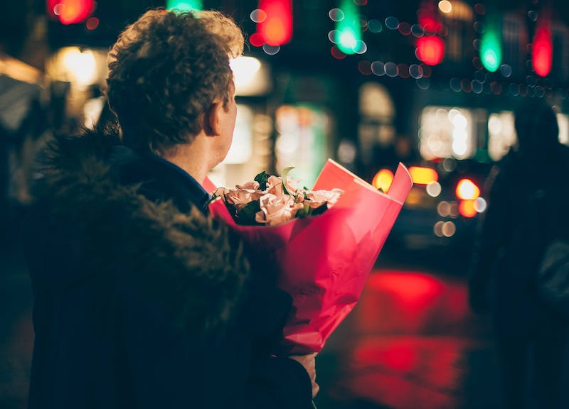 A guy holding a bunch of flowers facing a street.