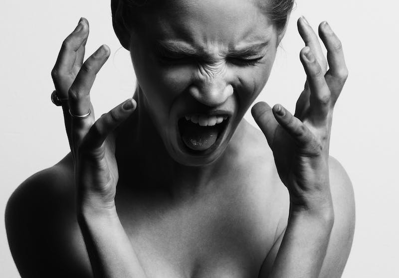 A black and white picture of a woman with no shirt on and hands up as she screams