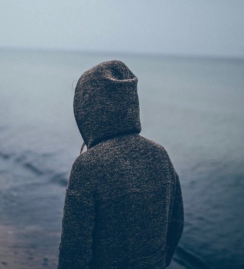 Girl with hoody at beach.