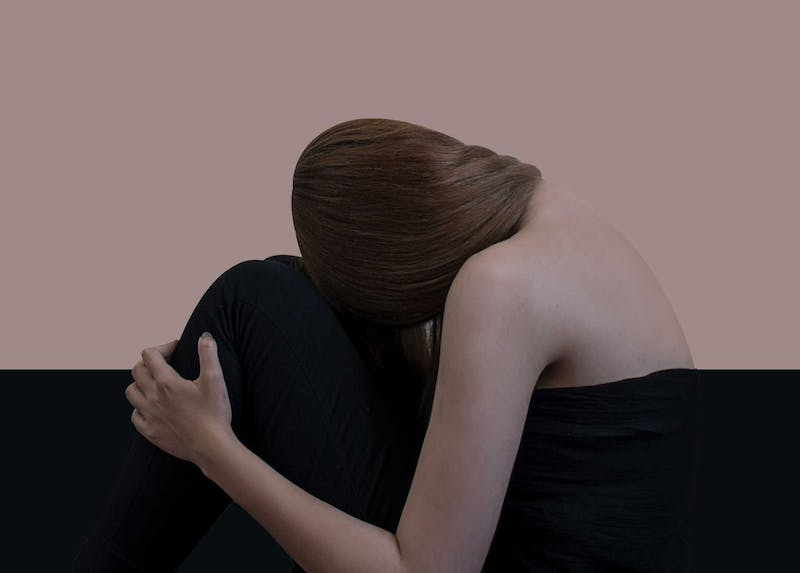 A woman with her head down against her knee while sitting down. Her face is not visible. Her arm is holding her leg and her red hair is swept over her shoulder away from the viewer. She is wrapped in black linen.