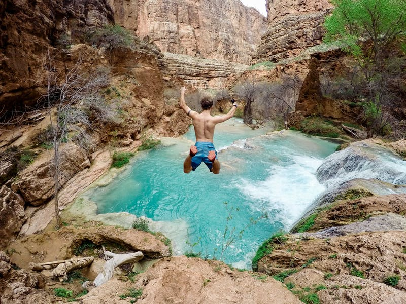 A guy jumping in a river from a cliff. The picture was taken from behind while he is still in mid-air.