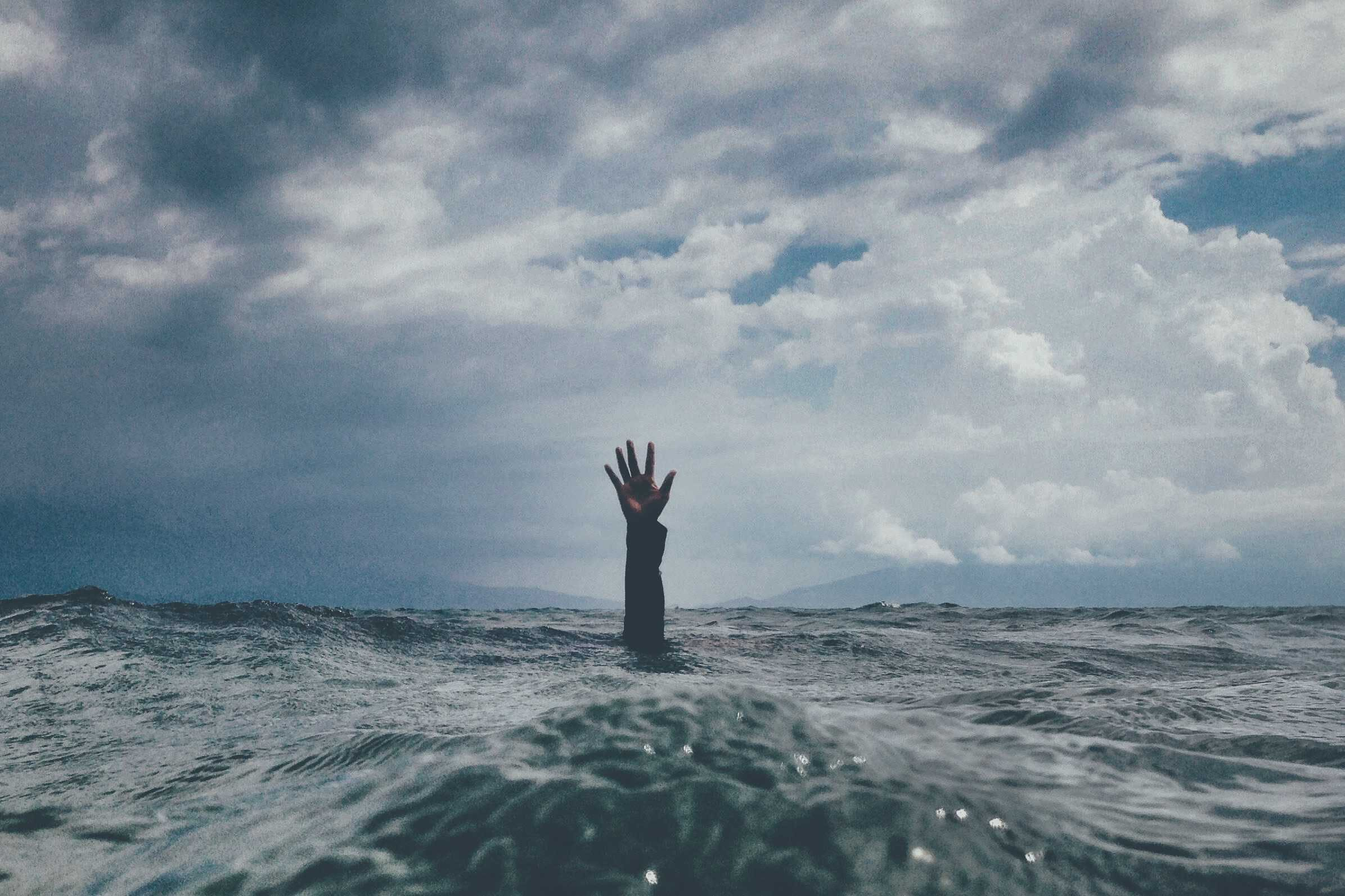 A person's visible hand reaching out from under the ocean's waters.