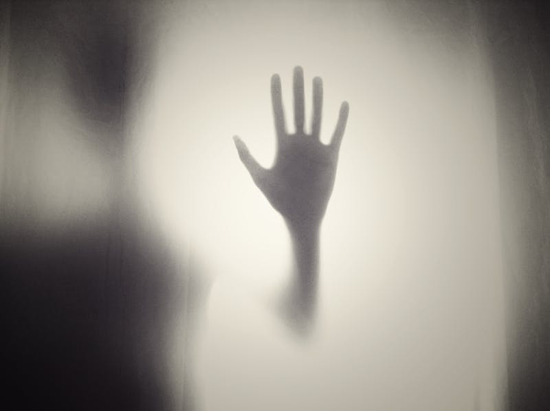 Hand silhouette against glass.