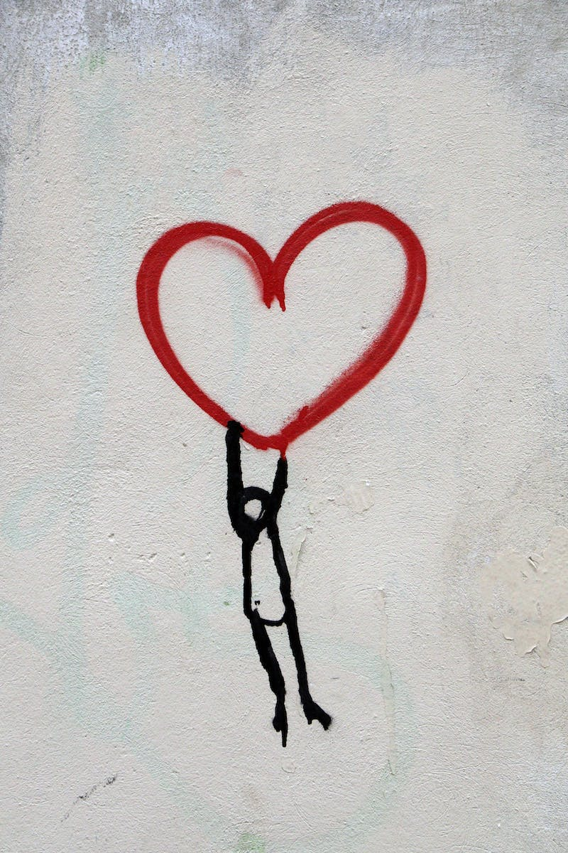 A stick figure hanging onto a heart.