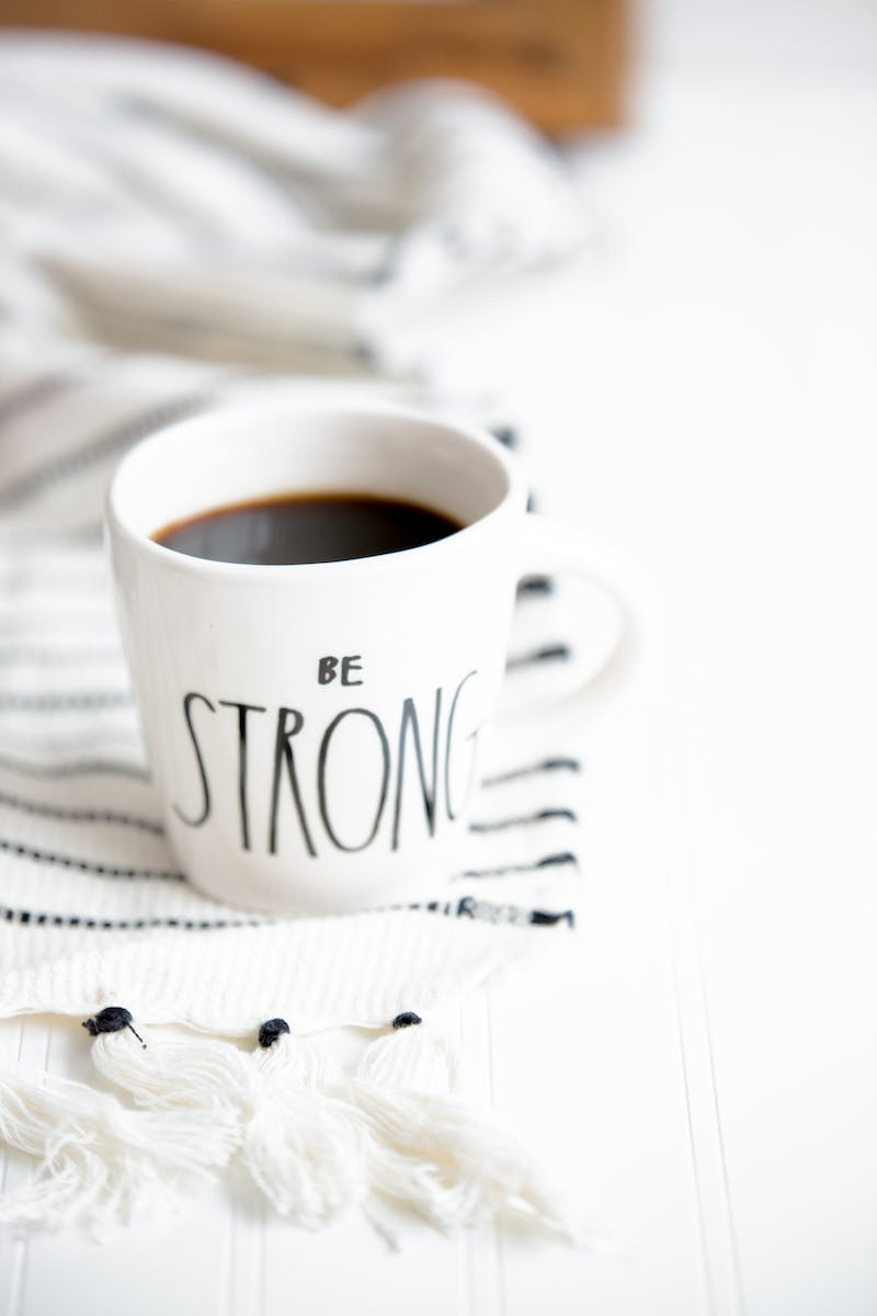 a  coffee mug on a white sheet with a saying on it saying Be Stong
