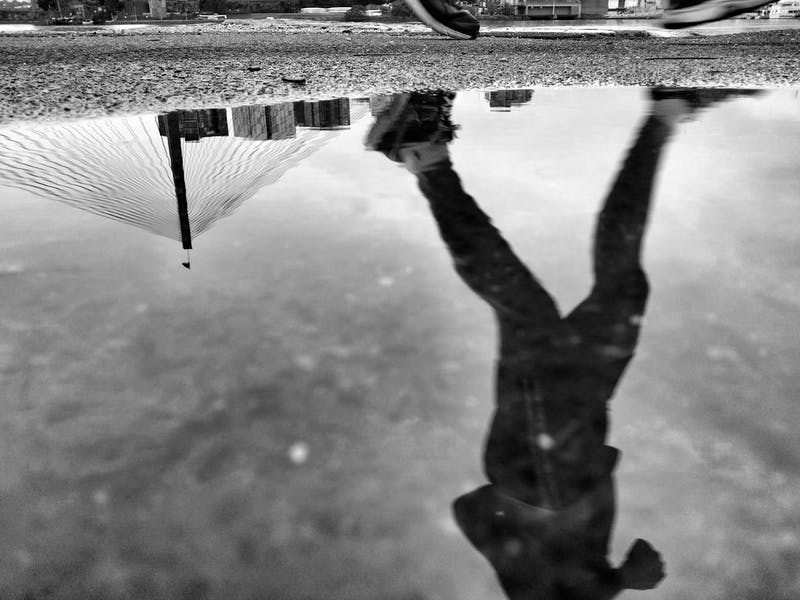A black and white picture of a man running with his reflecting in the water