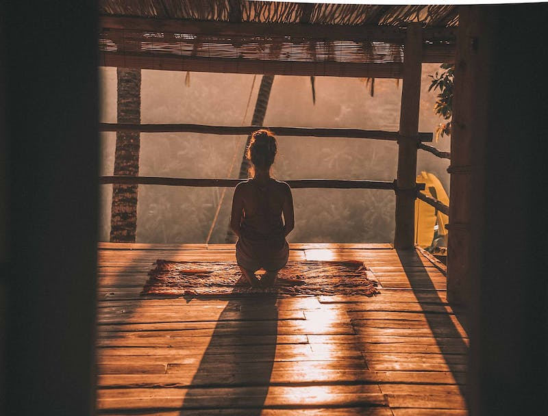 A young woman sitting meditating with her back to us in a wooden cabin