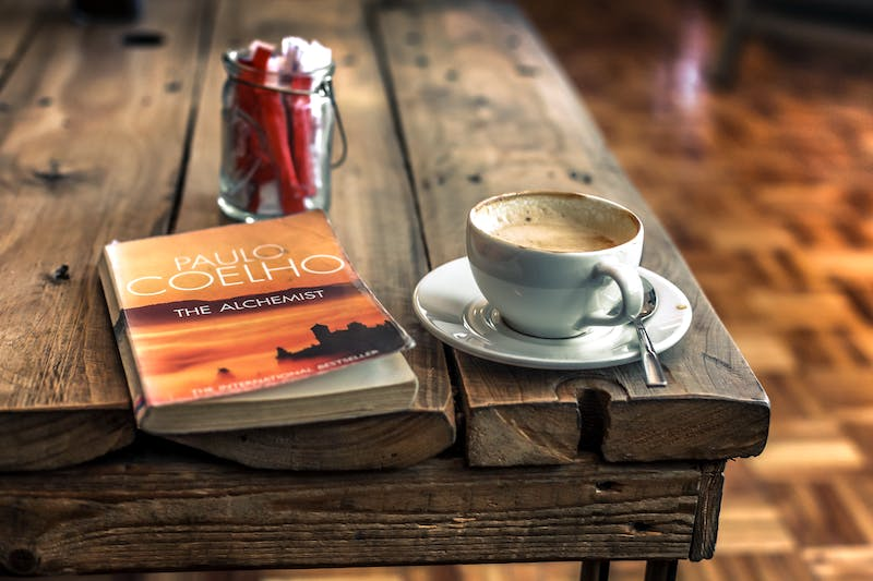 a Poaulo Coelho book the Alchemist on a coffee talbe alongside a cup of coffee
