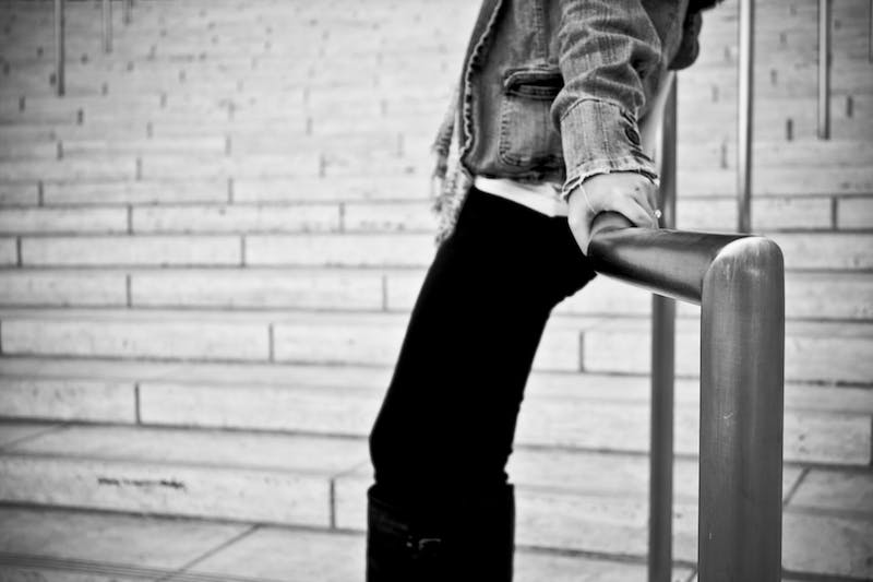 a black and white picture of a girl/boy leaning up against a railing wearing a denim jacket.  you can only see the torso