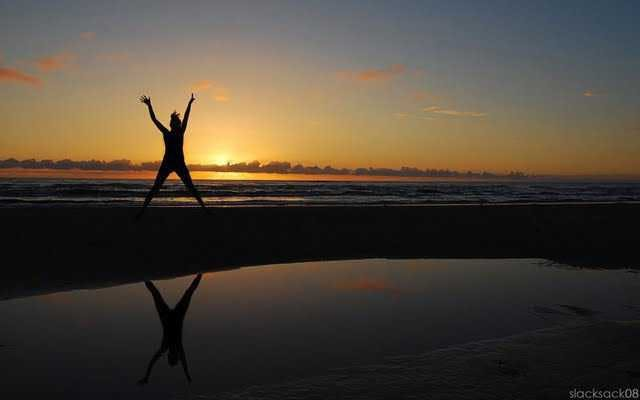 Woman jumping in X shape on beach with sunset in background.