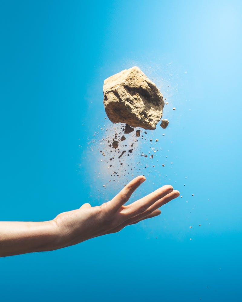 A hand throwing a clump of sand with a blue sky in the backgrownd