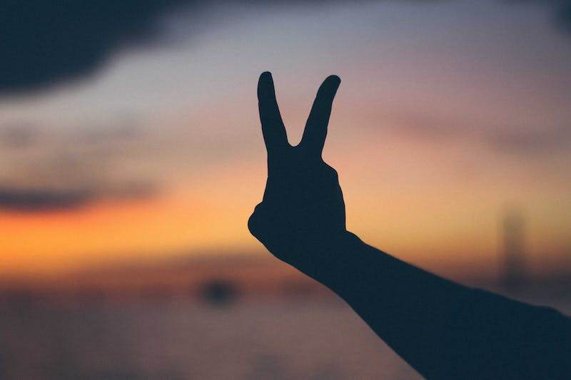 A person making a peace sign with their fingers.