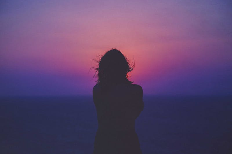 Silhouette of a girl looking into a pink sunset.