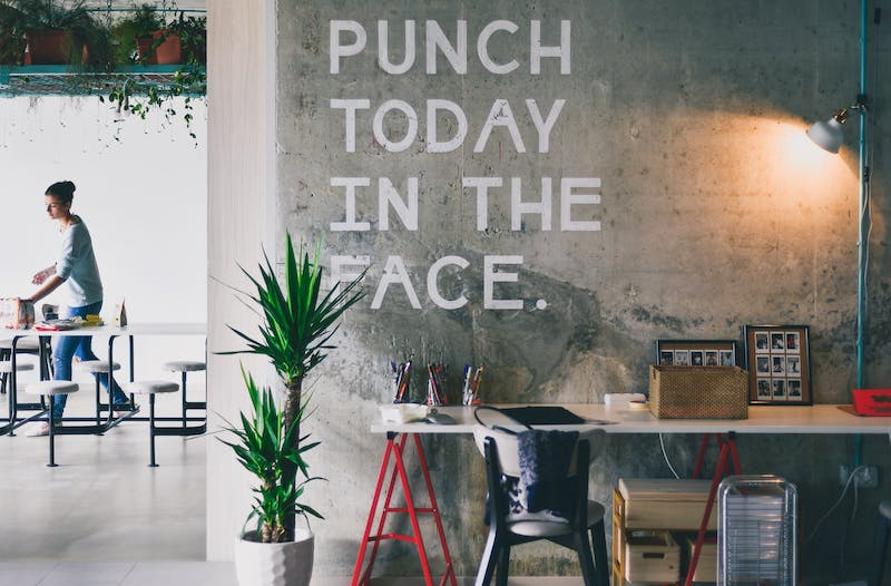 "A photo of a wall with painted text that reads, ""PUNCH TODAY IN THE FACE."". Looks like it is in a modern office."