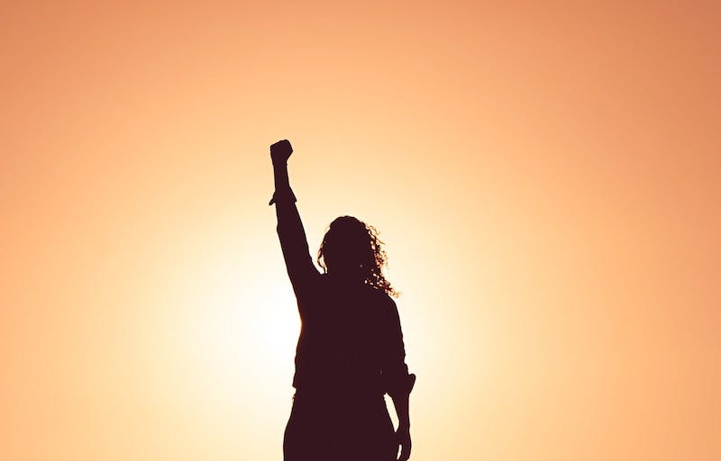 a silhouette of a woman holding up her right arm facing us