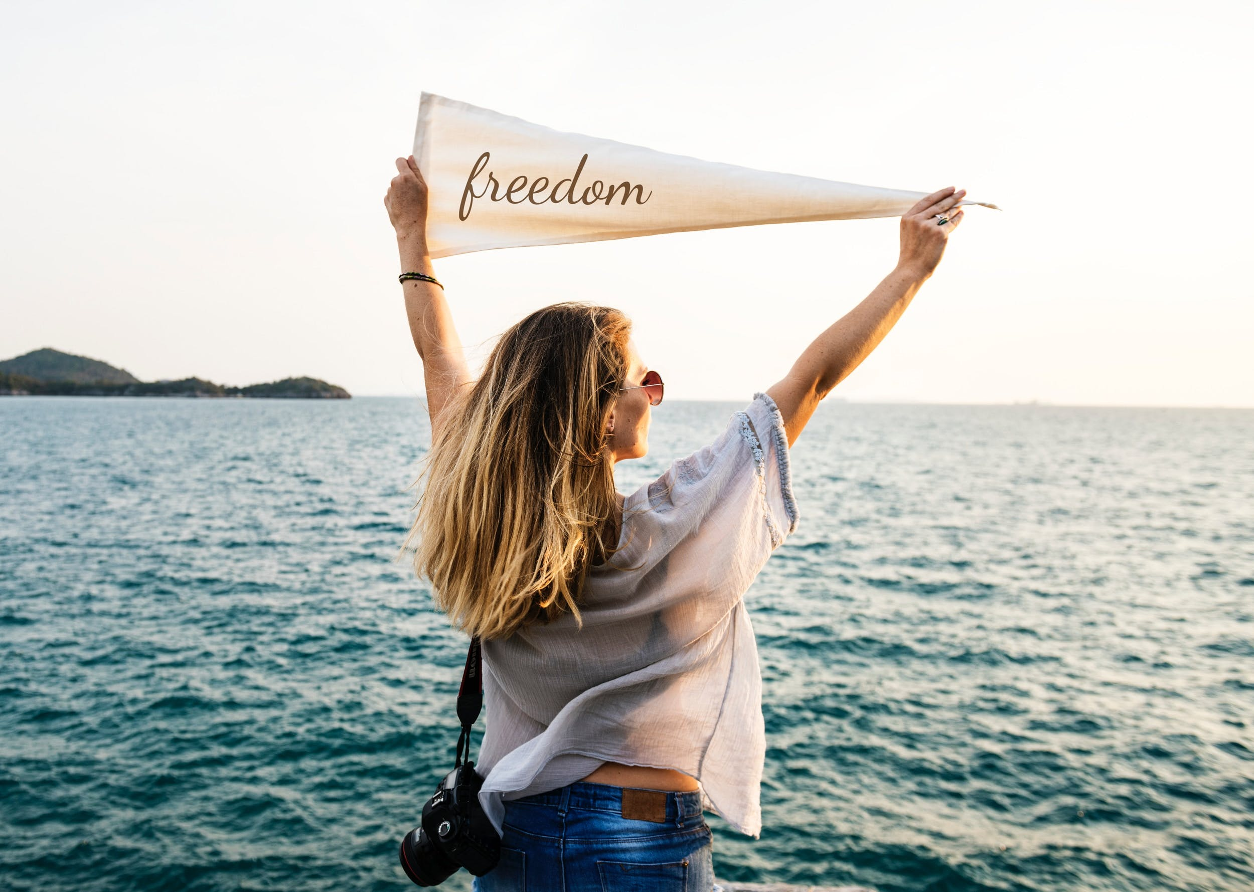 I woman with her back to us looking out at the ocean holding a banner saying freedom