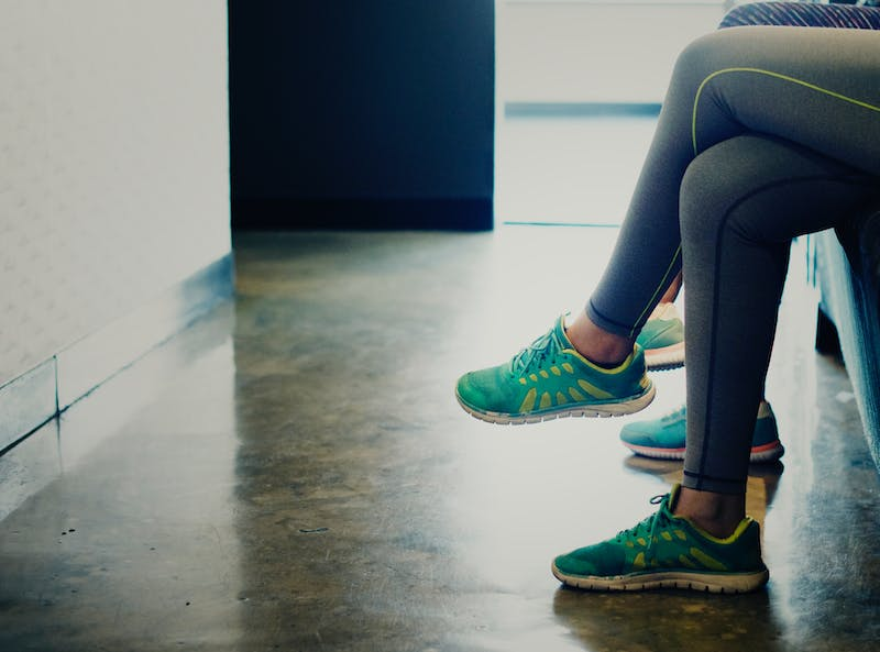 two girls sitting in running shoes and leggings.  You can only see their legs