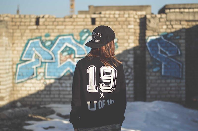 Teenage girl start at graffiti taken from behind