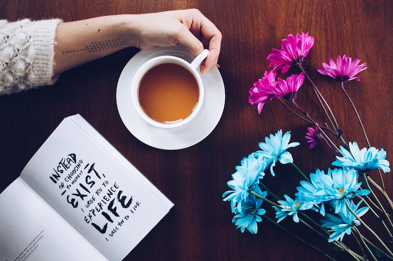 A womans arm touching a coffee mug with a book lying next to it  with some blue flowers on a desk