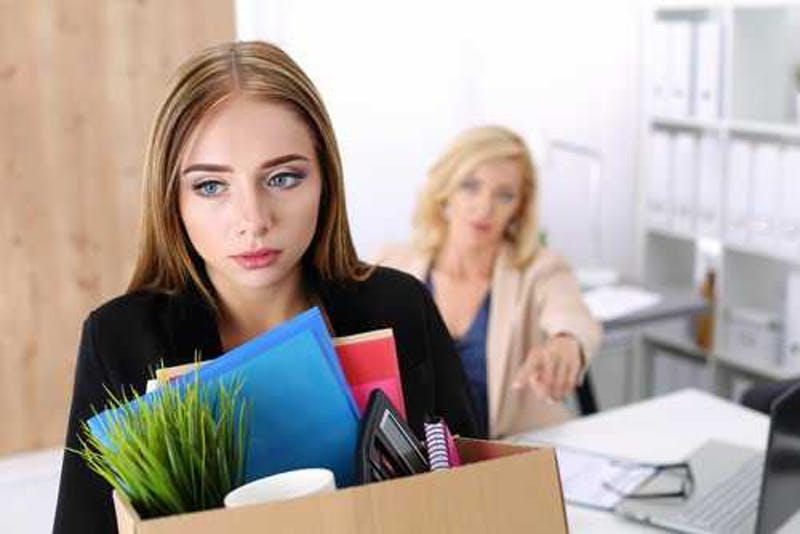 Two girls in a room. One standing with back to the other with files in hand. Picture taken in an office. Looks like the woman with her back to the other has just lost her job.
