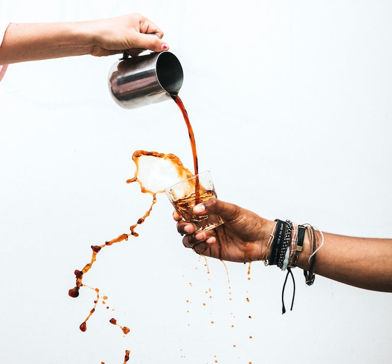 two hands with a white background pour coffee from a jug into a cup