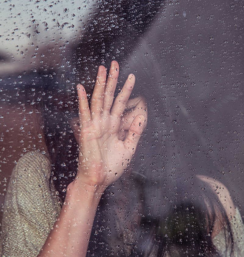 Upset girl in window.