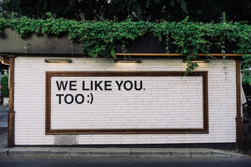 "Text on a wall that reads ""WE LIKE YOU TOO.""."