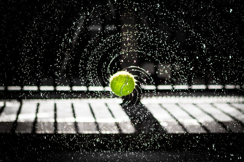 A wet tennis ball in mid-air.