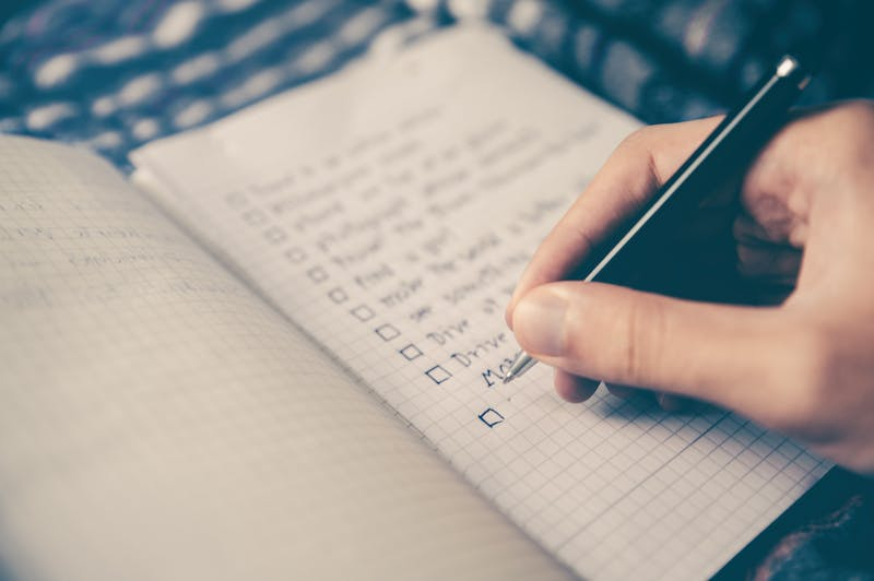 Someone writing a checklist in a notebook.