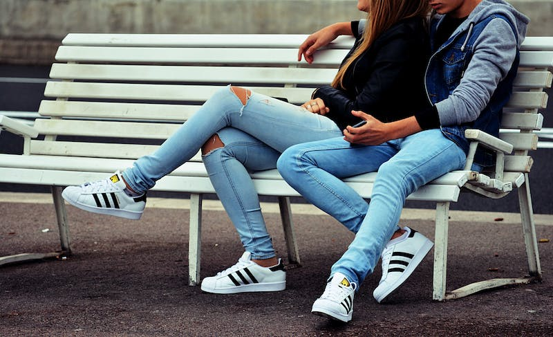 A young couple in jeans sitting on a bench.